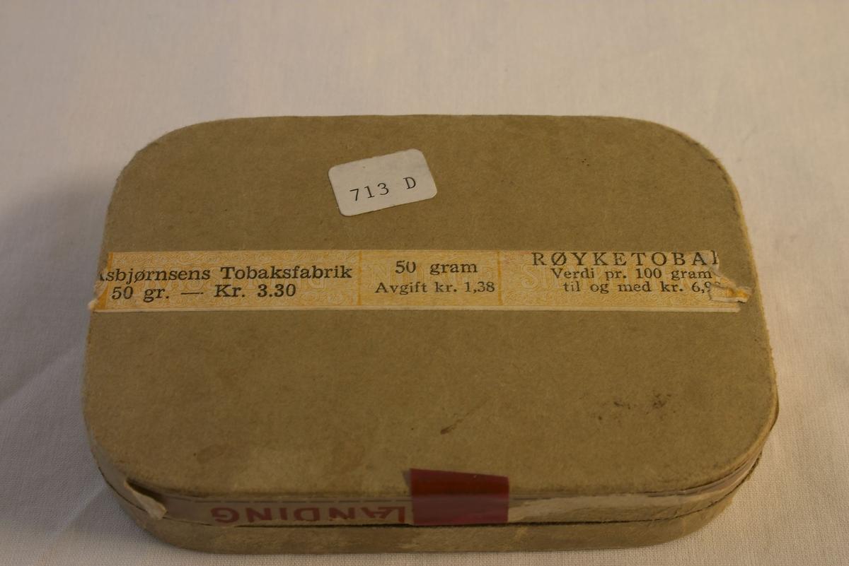 """4 esker, 1 med tobakk. A: Grålig oval eske med blått papirband rundt, hvor det står med kvite bokstaver: """"KRIGSBLANDING"""". I denne esken finnes det tobakk fra 1. verdenskrig. L: 10,6 cm, B: 7,4 cm. B: Grålig oval eske med grønn topp hvor det står: """"PETTERØE'S BLANDING 2"""" og finkarvet - ekstra lett samt et rødt billede av en bulldog. Nederst rundt esken en blå farge. Det finnes ikke tobakk i denne eske. L: 10,5 cm, B: 7,6 cm. C og D: Grålig rektangulære esker hvor det på toppen finnes røde striper rundt kanten, samt et rødt bilde av en røykende rev. Med røde og kvite bokstaver står skrevet """"ASBJØRNSENS EVENTYR BLANDING"""" FINT SNITT. Fabrikert hovedsakelig av naturlige nikotinfattige tobiakker - ikke kjemikaliebehandlet. A. Asbjørnsens Tobaksfabrik Christianssand S. Ingen tobakk i disse esker. L: 11,5 cm, B: 8 cm."""
