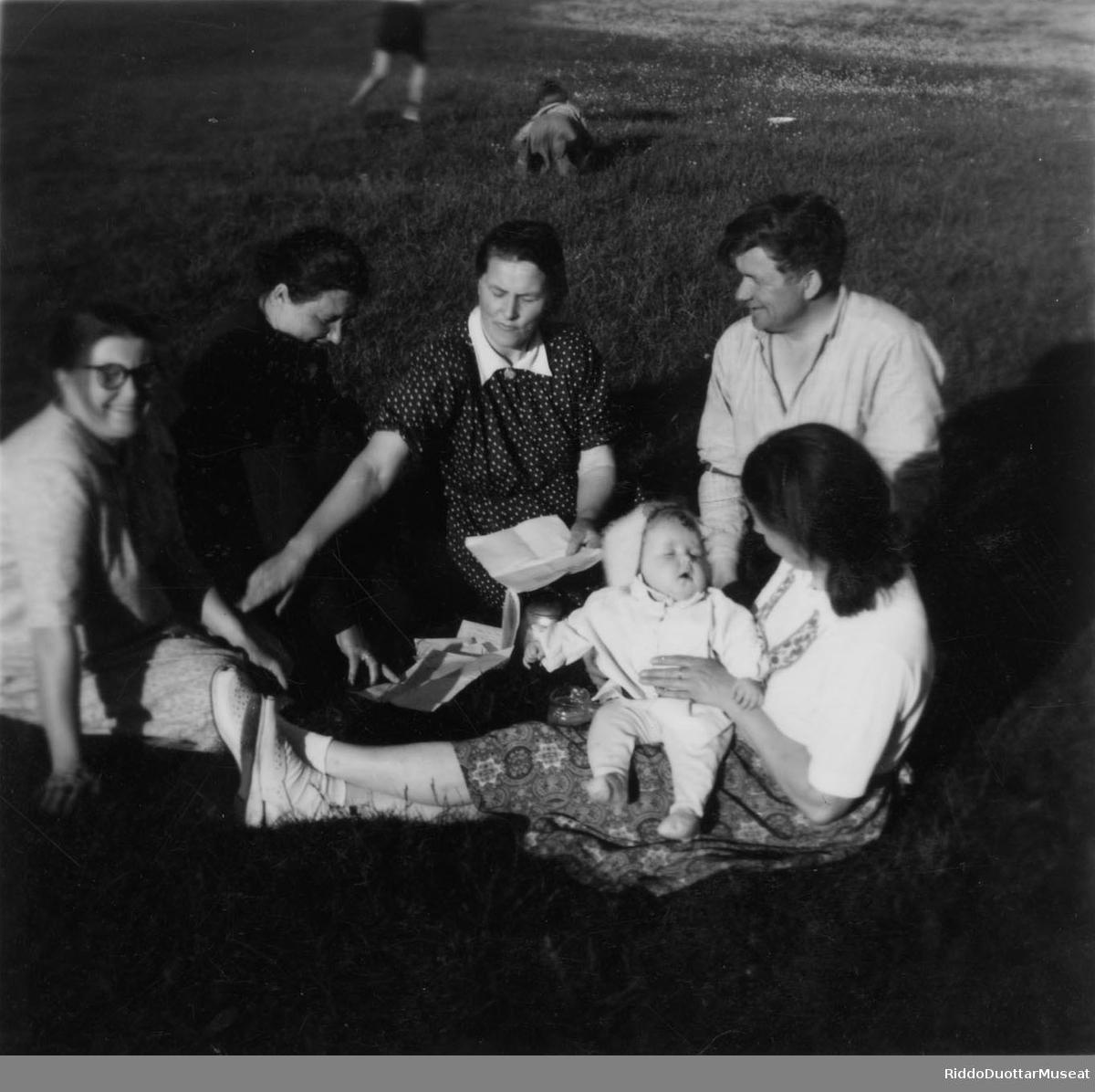 Nissonolbmot, mánát ja dievdoolmmoš cohkkajit giettis. Kvinner, barn og en mann sitter på en plen.