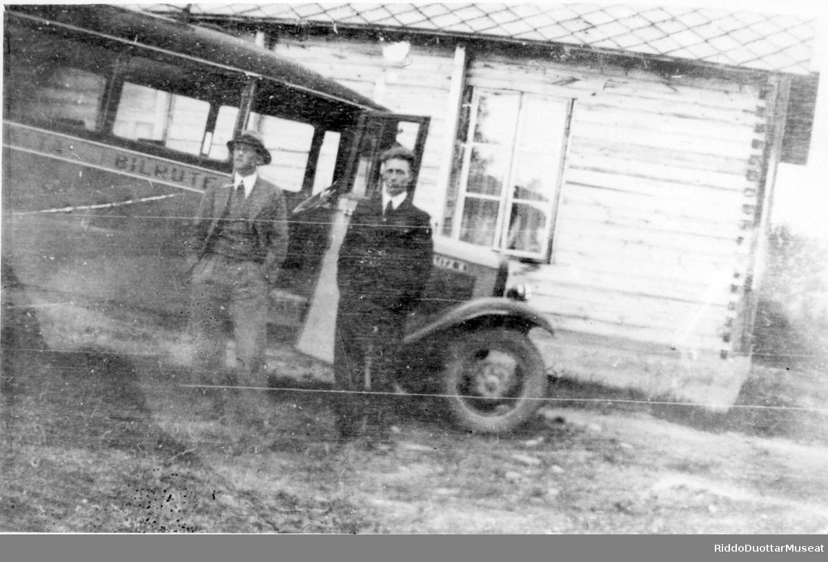 Dievdoolbmot cuožžuba biilla guoras, dimbbarviessu duogabealde. To menn foran et bil og et tømmer hus i bakgrunnen.