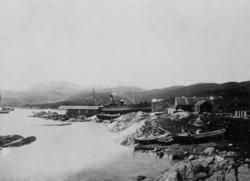 Dampskip på slipp, med nordlandsbåter i fjæra i forgrunnen.