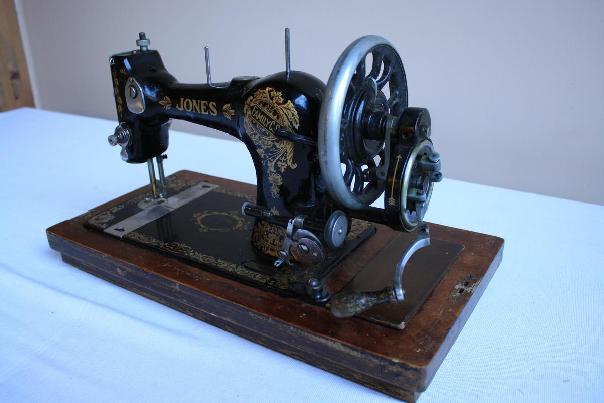 Symaskin med handsveiv på tresokkel. Verktøyskrin intregrert i tresokkelen. Heile maskina er dekorert  med blomster, blad og div. mønster i raudt og gult. Lokk i tre følger med.