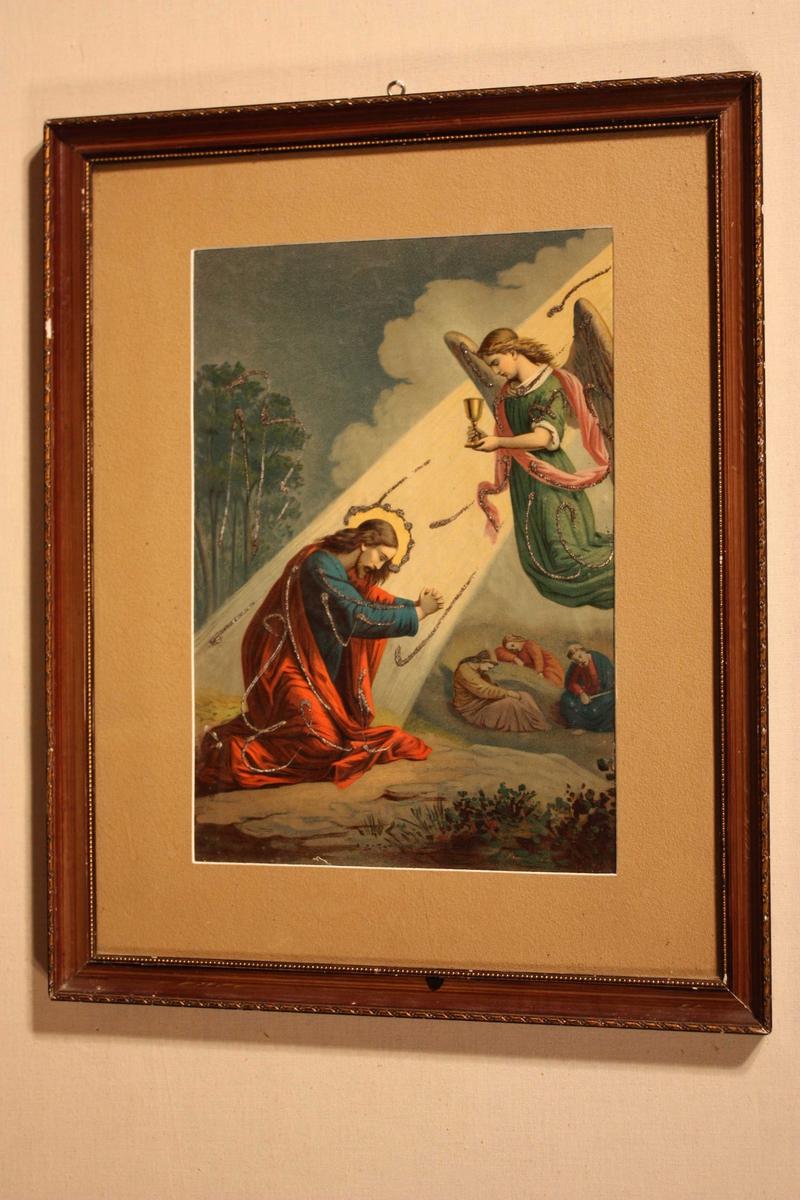 Brunbeisa biletråme med trykk (teikning) av Jesus på hyrdingmarka med glorie og raud kappe.  Han ligg på kne og tek imot kalken frå ein engel. Glitter markerer glorie, kape, hyrdingstav, engel m.m.  Brun paspartout rundt biletet.  Augekrok til oppheng på toppen av råma.