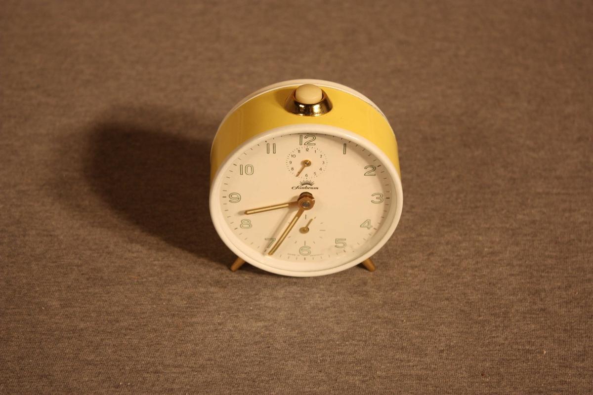 Rund  manuell vekkjarklokke med stoppeknott på toppen.  Står på to bein og ei baktstøtte. På talskiva er ei miniskive for minuttvisar og ei for alarmtid.