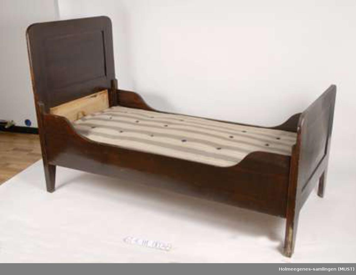 Enkeltseng av furu med rammemadrass. Gavlene og sidevangene monteres sammen med sengebeslag. Hode- og endegavl har to fyllinger av furu. Sidevangene er lavere på midten.