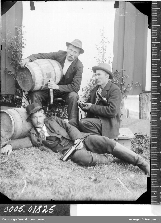 Gruppebilde av tre menn med vintønner og flasker.