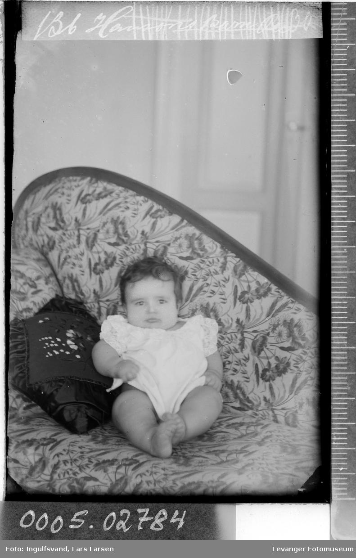 Portrett av et lite barn i en sofa.