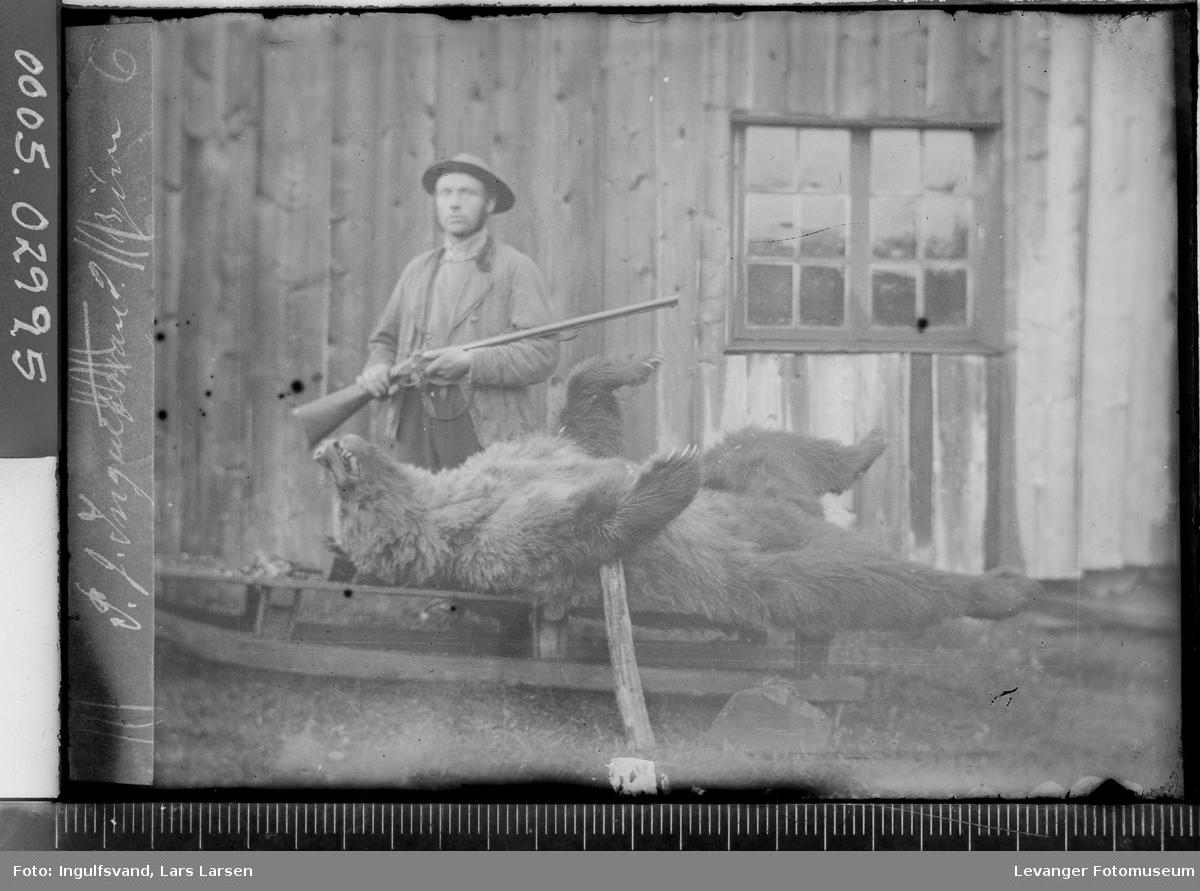 Portrett av en jeger med en død bjørn på slede.