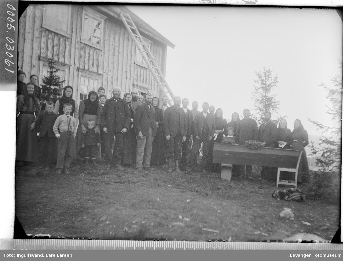 Forsamling av mennesker med kista før begravelsen.