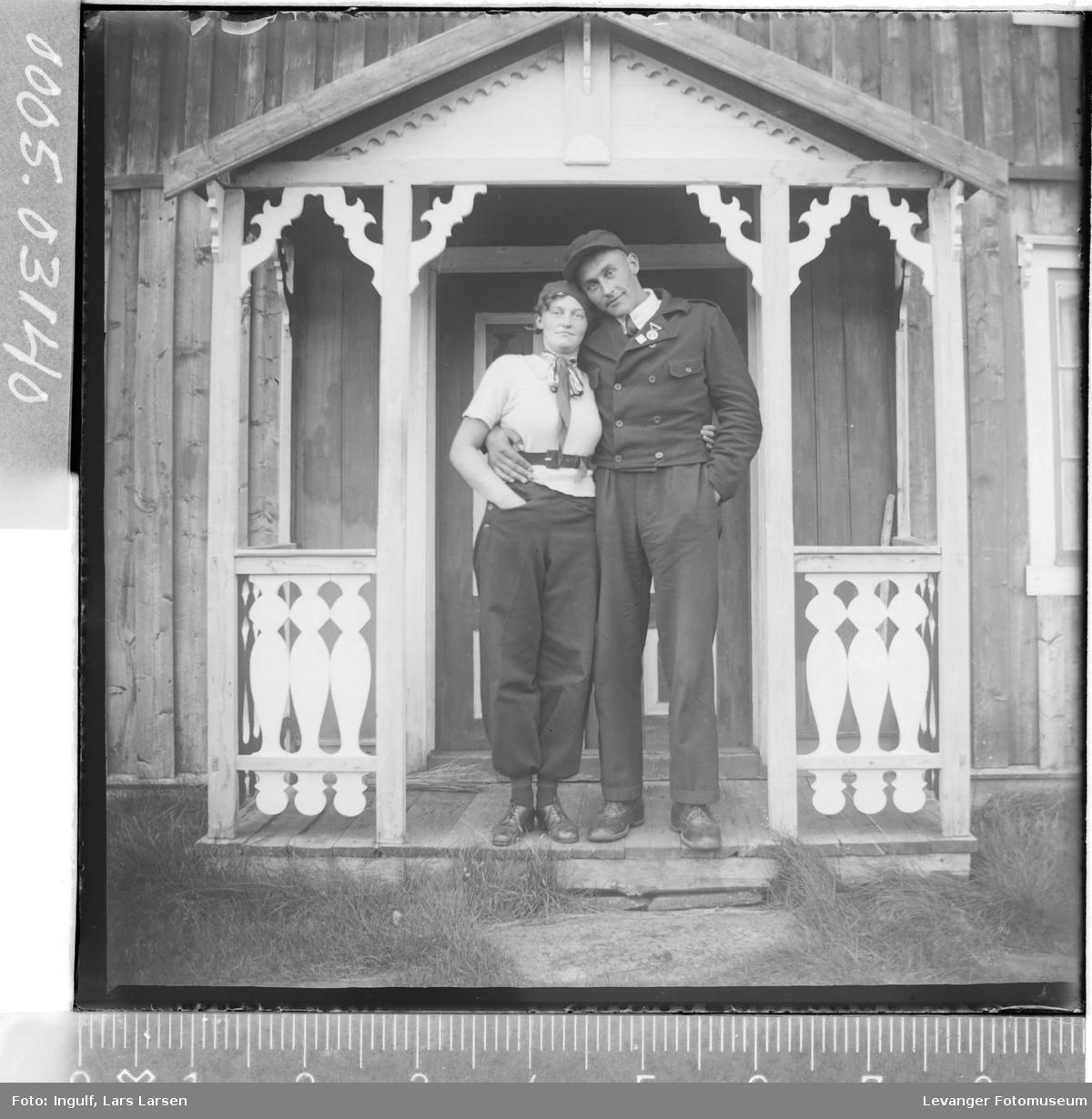 Portrett av kvinne og mann ved et inngangsparti.