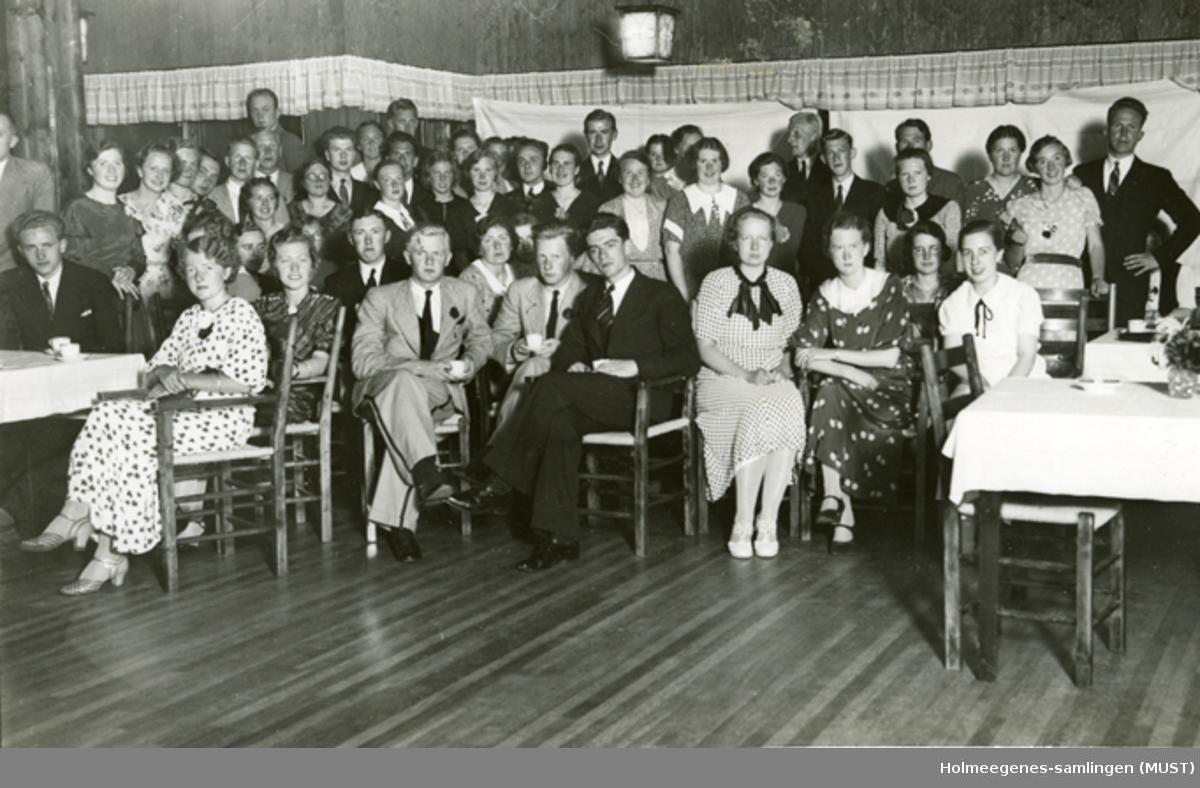 Gruppebilde, unge kvinner og menn i et festlokale. Muligens i forbindelse med russefeiring.