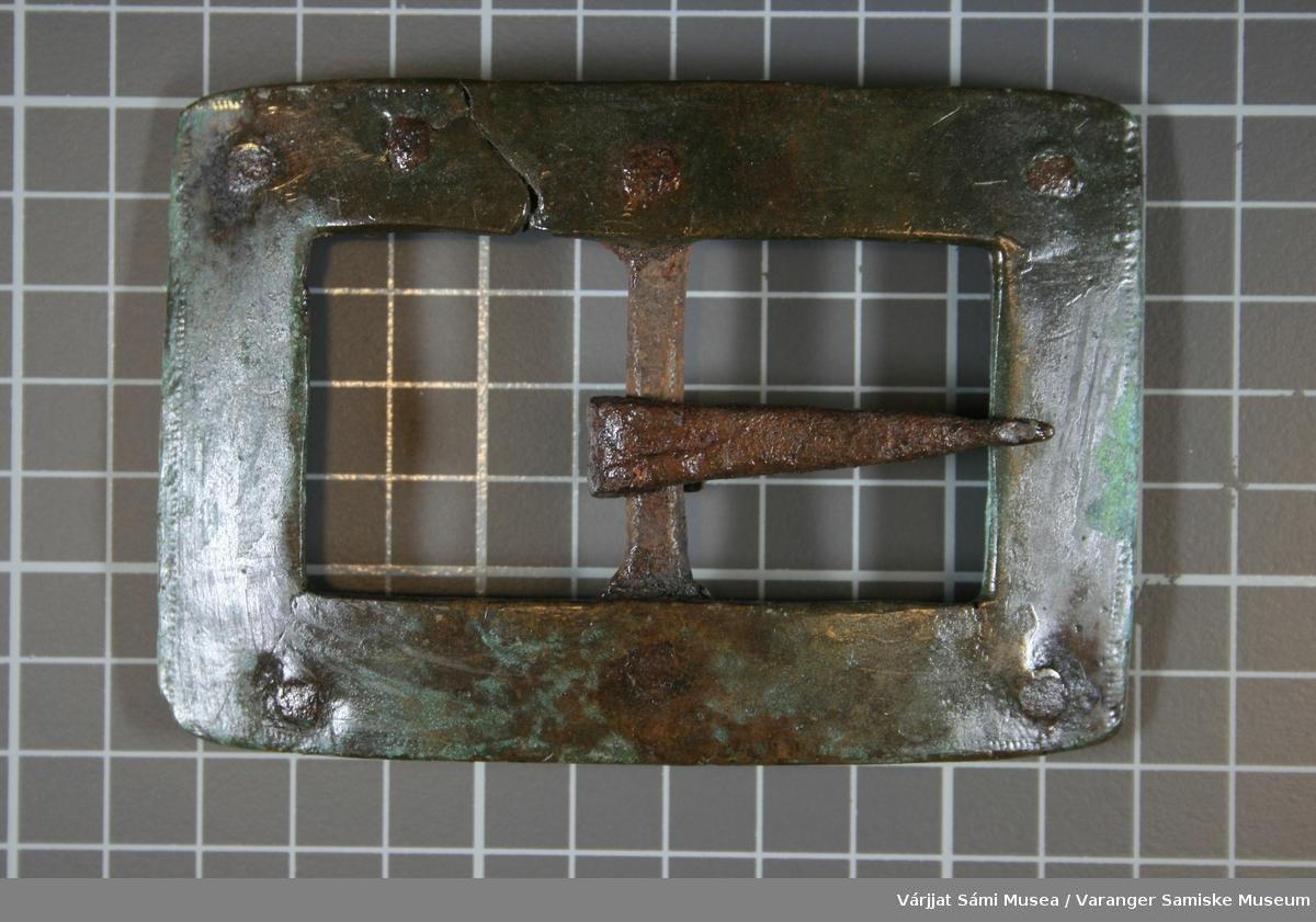 Rektangulær beltespenne av metall; Jern og kobber/bronse. Den er i solid utførelse. Spennen er grålig med grønnaktige innslag. Delen som er av jern er rustet.