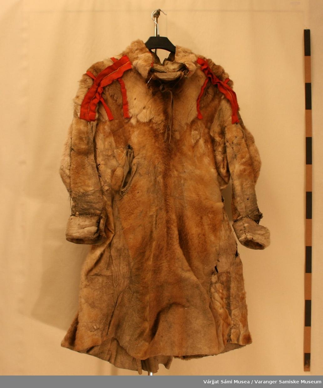 En damepesk (muoddá) av reinskinn.  På skuldrene er den pyntet med rødt klede og en gul smal klede stripe på hver skulder. På ryggen er det 6 røde klederenner og framme er det tre igjen- en har ramlet bort. I halsen er det skinnreimer som kan snøres igjen.