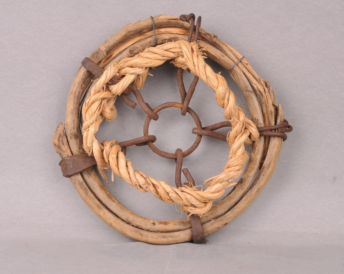 Snodde og usnodde vidjeband som dannar ei ringforma truge. Mot botnen av truga er det festa ein smidd jernring, som så er festa med fem korte jernlekkjer.