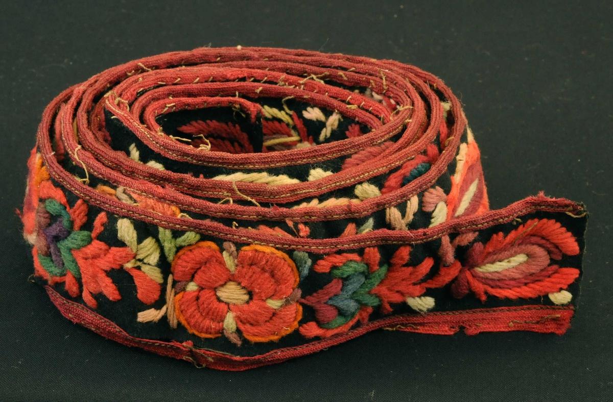 """Bord av svart vadmål. Rosesaum (plattsaum) av laust ullgarn i mange fargar, """"hallingsaum"""". Borden er kanta på begge langssidene med raudt band."""