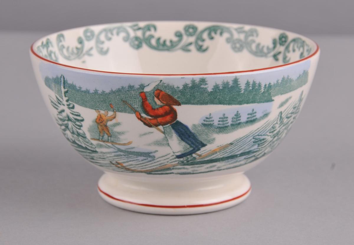 Bolle med dekor i grønt/blått/gult/raudbrunt. Ein mannleg og ein kvinnelg skiløpar. Ein grønmåla akantusbord på innsida av bollen.