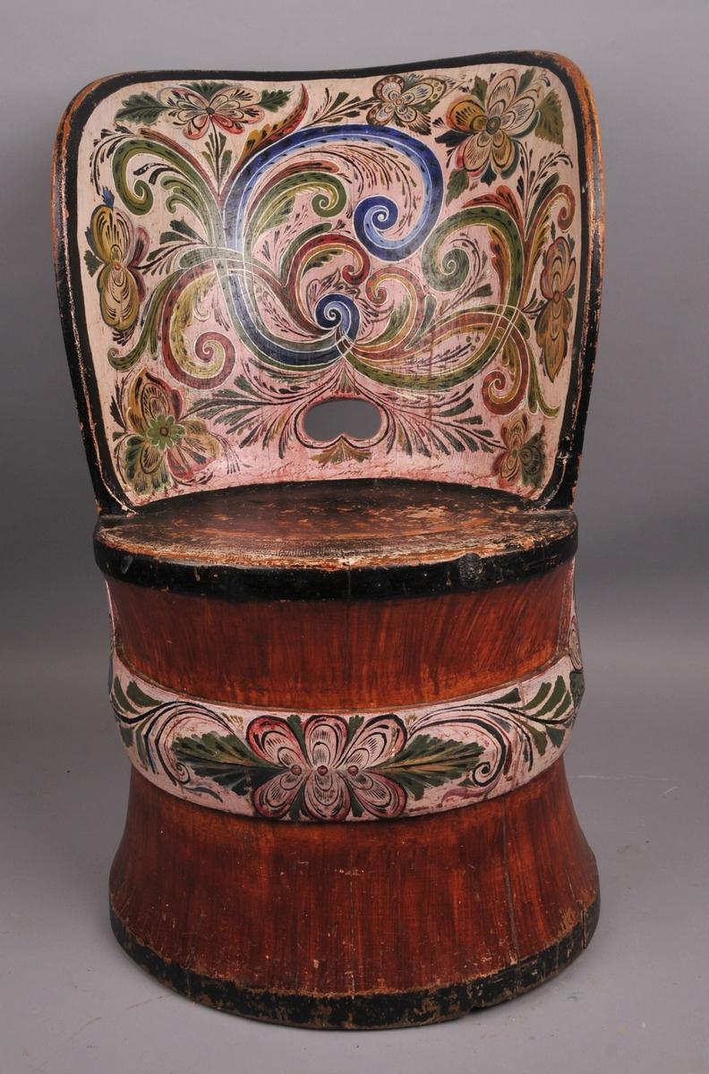 Stor kubbestol. Måla i raudbrun farge med svart sete og kantar. Ryggen innvendig og pyntebelte under setet og rundt stolen er måla i ljos rosafarge med rosemåling i blått, grønt, raudt, gult og svart.