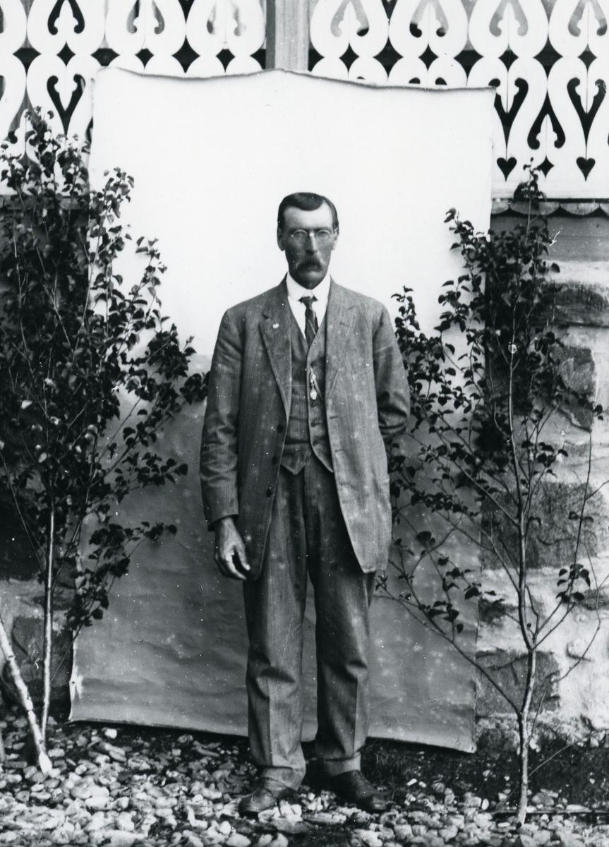 Dresskledd mann med briller, i helfigur, foran lerret på veranda