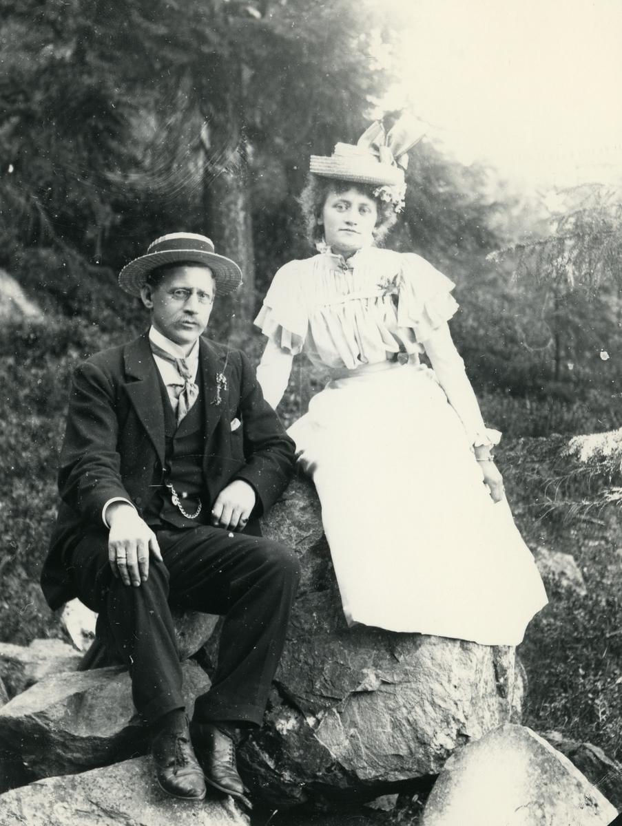 Mann i dress og hatt, og kvine kledd i lys kjole og hatt, med blomster i håret, fotografert på steiner i skog