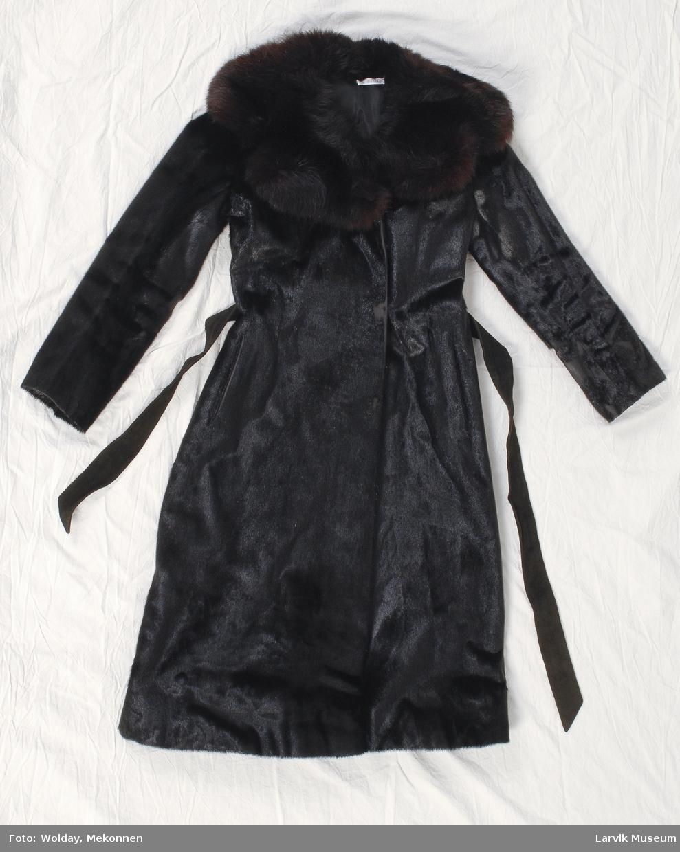 Form: Smal kåpe i pels med kort skinn, buskete revepels rundt halen. Belte i semsket skinn, knytes. innvendig belte også, og hemper for lukking. Fløyel inni lommene.