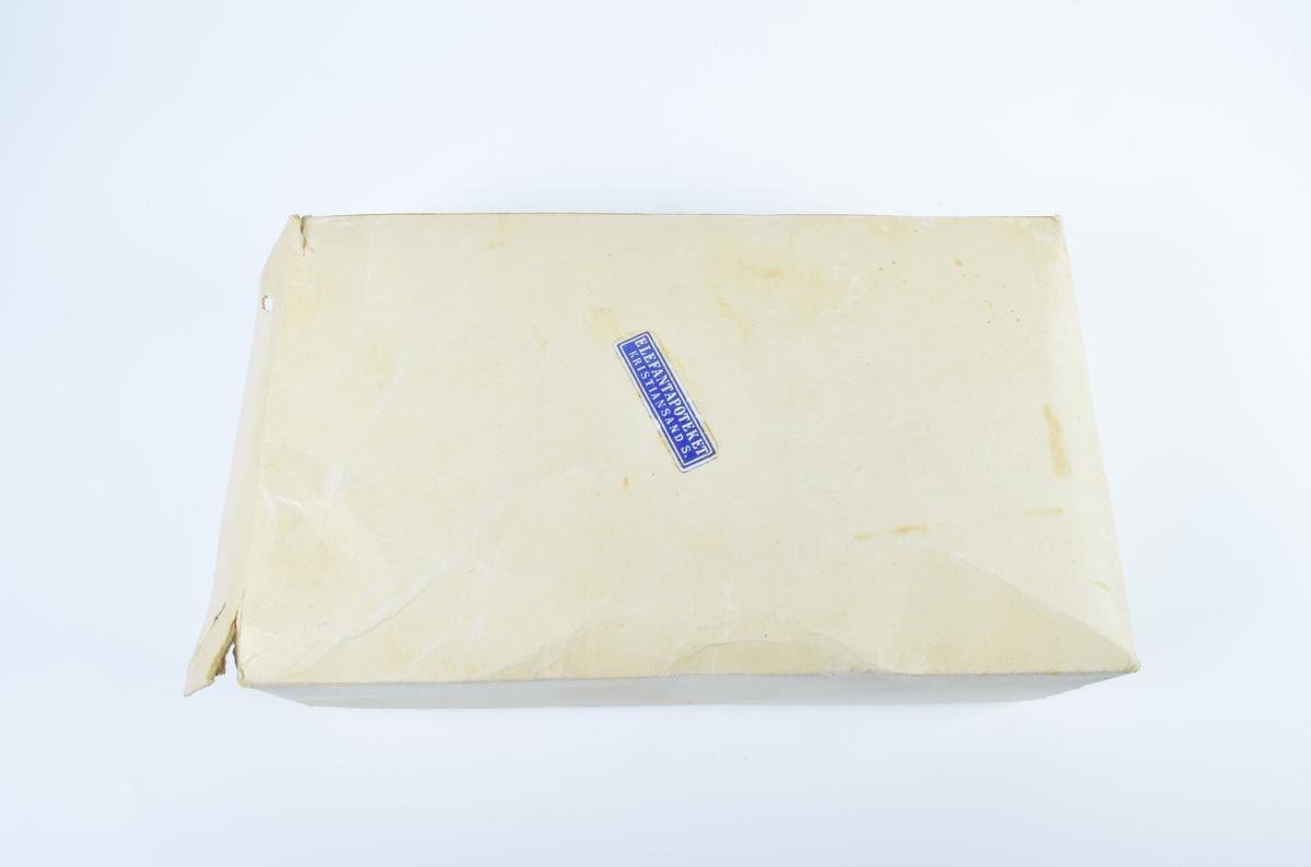Åpnet eske av hvit papp som inneholder smale, rektangulære, blå etiketter med hvit, dobbel bord og hvit tekst. Esken er full.