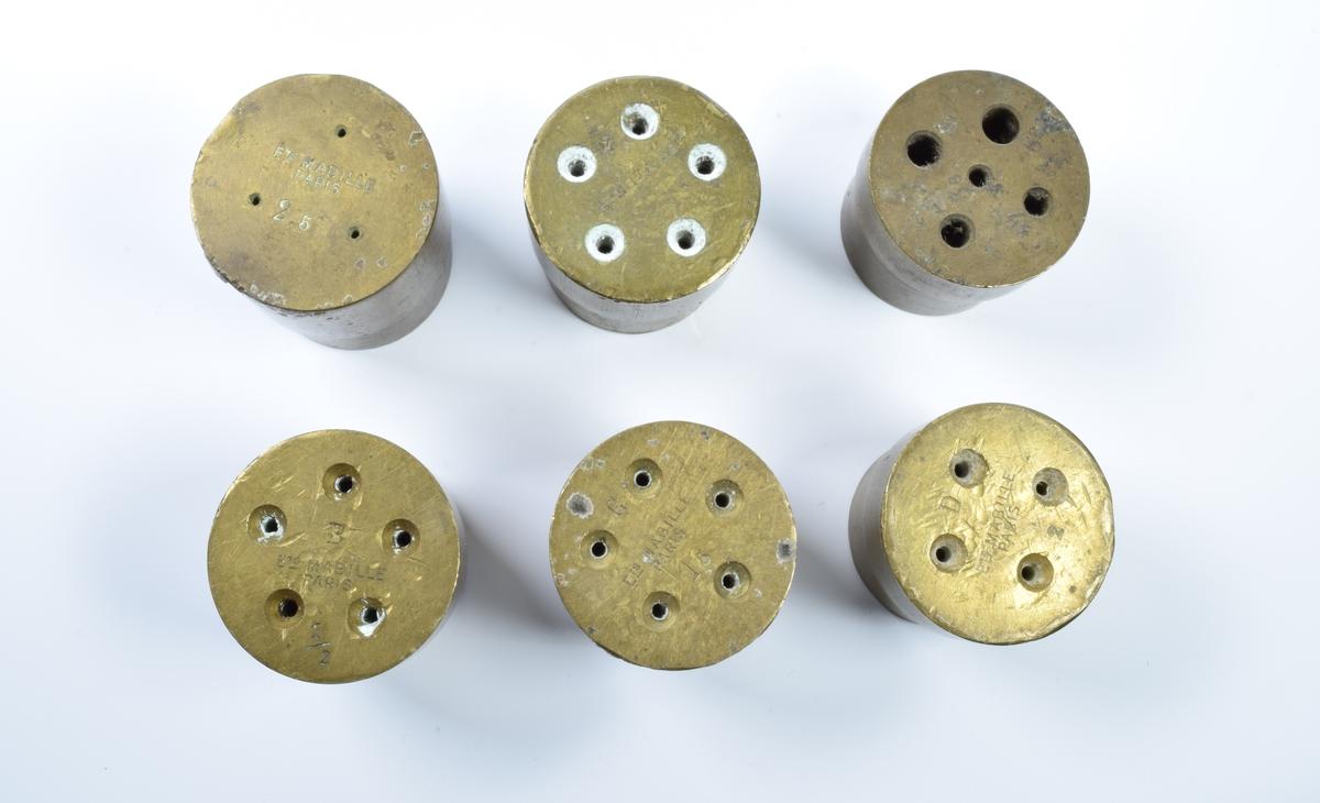 """Seks former til tablettfremstilling. Formene har mellom tre og seks hull som går tvers gjennom formene. Hullene er store på """"baksiden"""" og smaler av frem til forsiden hvor de er mye mindre.  Formene skal brukes i en tablettfremstillingsmaskin."""