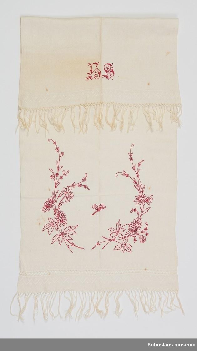 """Tuskaftsvävt linne,som i båda ändar övergår i ett kort stycke mönsterväv. Vid ena ändan centimeterbred bård utan inslag där varpen  knutits i dekorativt mönster. Avslutas ibåda ändar av knuten frans. Konturbroderi i stjälkstygn i rött föreställande blomrankor och en fjäril. I andra ändan monogram """"LS""""."""