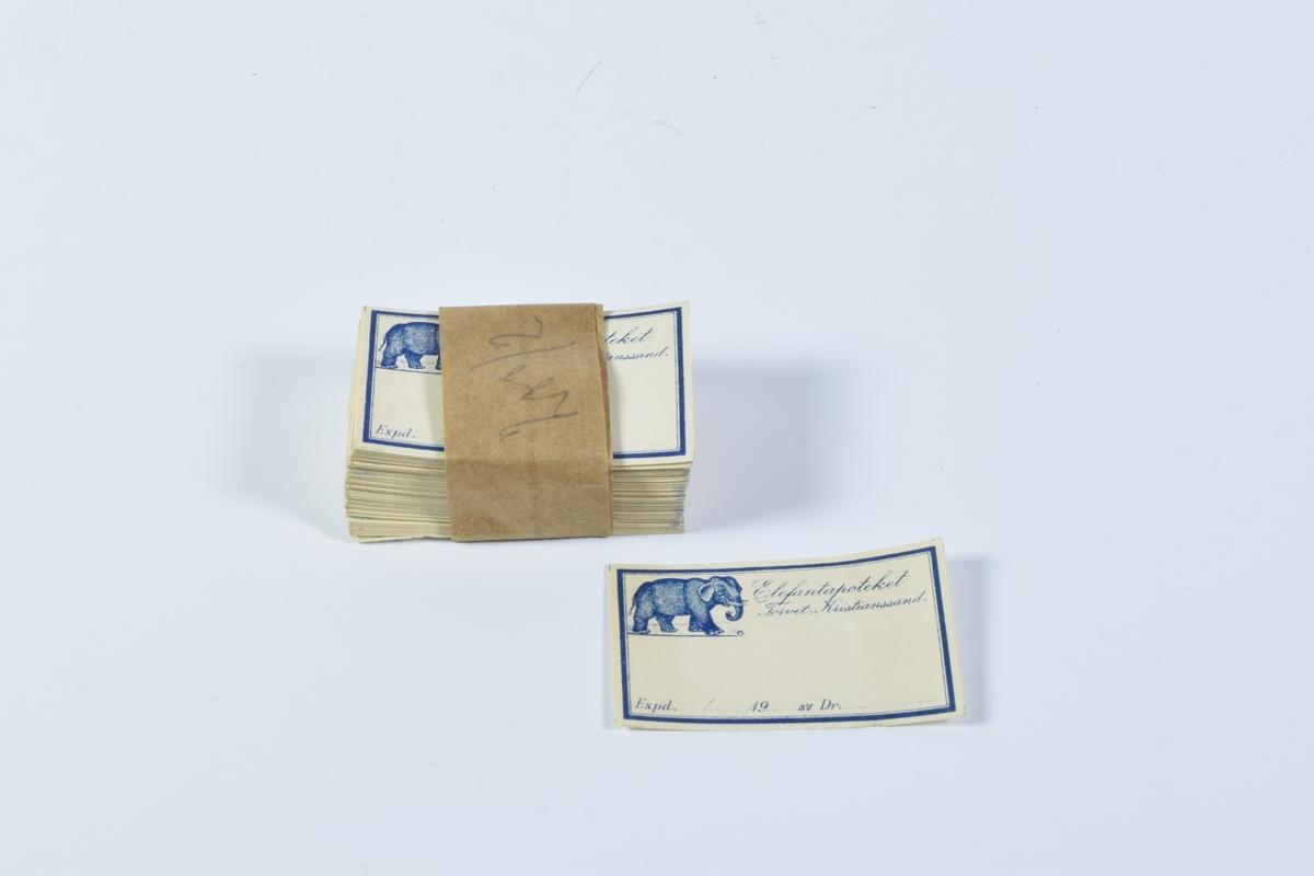 """Liten bunke med etiketter. Bunken er holdt sammen av et brunt papirbånd.  Etikettene er liggende og rektangulære med en halvtykk blå bord rundt kanten. På innsiden av borden i det øverste venstre hjørnet er det bilde av en elefant. Til høyre for elefanten står det """"Elefantapoteket, Torvet, Kristiansand S."""" med løkkeskrift. Etikettene er hvite med blå skrift."""