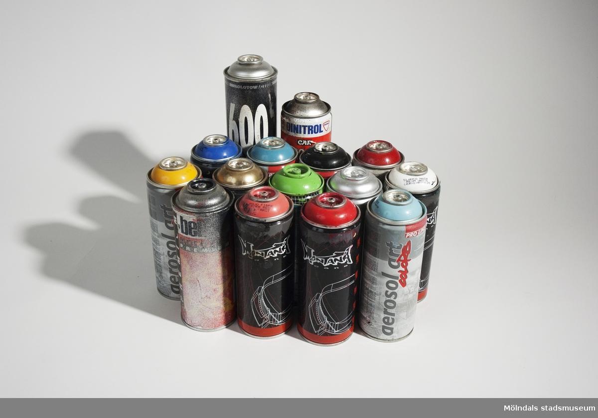 Samling av sprayburkar som används av graffitimålare. Totalt 15 burkar varav 1st Molotow artist, 1 st Molotow premium, 6 st Montana cans, 5 st Aerosol art - proline, 1 st Dinitrol rostskydd samt 1 st blank. Burkarna varierar i storlek mellan 17,5 x 6,5 cm och 24 x 7 cm. Spraymunstyckena är borttagna. Förvarades i ryggsäck 05004.