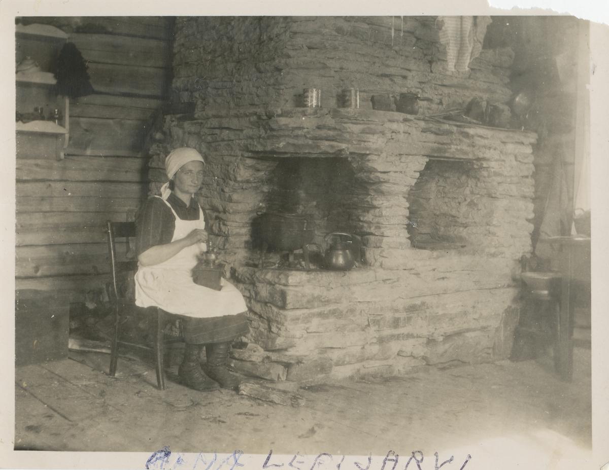 En kvinne sitter ved peisen i sitt hjem og kverner kaffe.