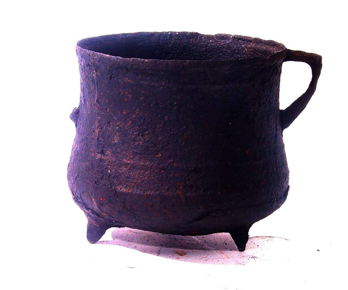 Gryte av jern. Potteform med innsvungne sider, svakt rundbunnet på 3 spisse føtter. En  ørehank,  den annen avslått.