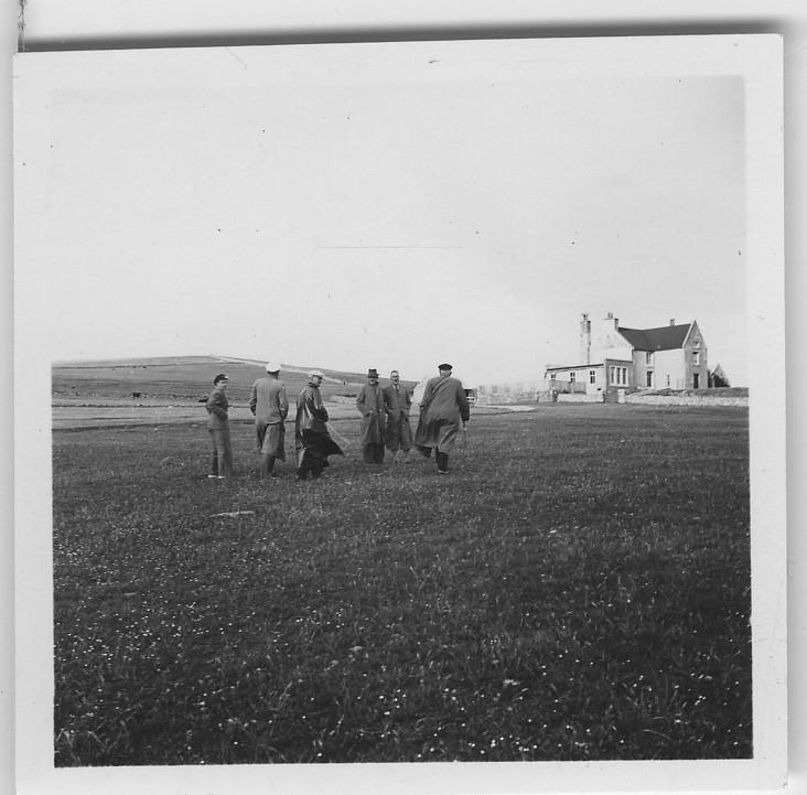 'Från ''Skageraks''-expeditionen till Hebriderna och Shetland: ::  :: 6 personer (män) gåendes mot ett hus på en äng. Enligt anteckning på baksidan av fotografiet: ''På väg till té hos Sandisons''. ::  :: Ingår i serie med fotonr. 4111:1-43.'