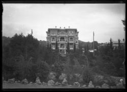 'Stort hus på avstånd, med balkonger. Framför huset staty ev
