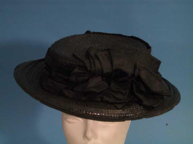Flatpullet, bred stråhatt med et bredt sort bomullsbånd omkring, med en stor sløyfe.  Sort   strå med bomullsbånd i sort.  Innvendig sort lerretsfor og forretningsmerke: Marie Nielsen Modeforretning.