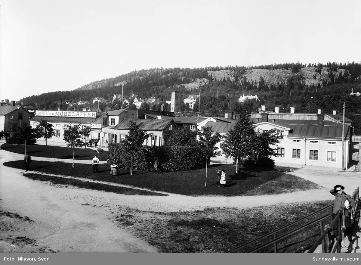 Vy över Norrmalm, taget från Puckelbron. Skepparegatan. På gräsytan står två karamell- och ballongförsäljerskor.