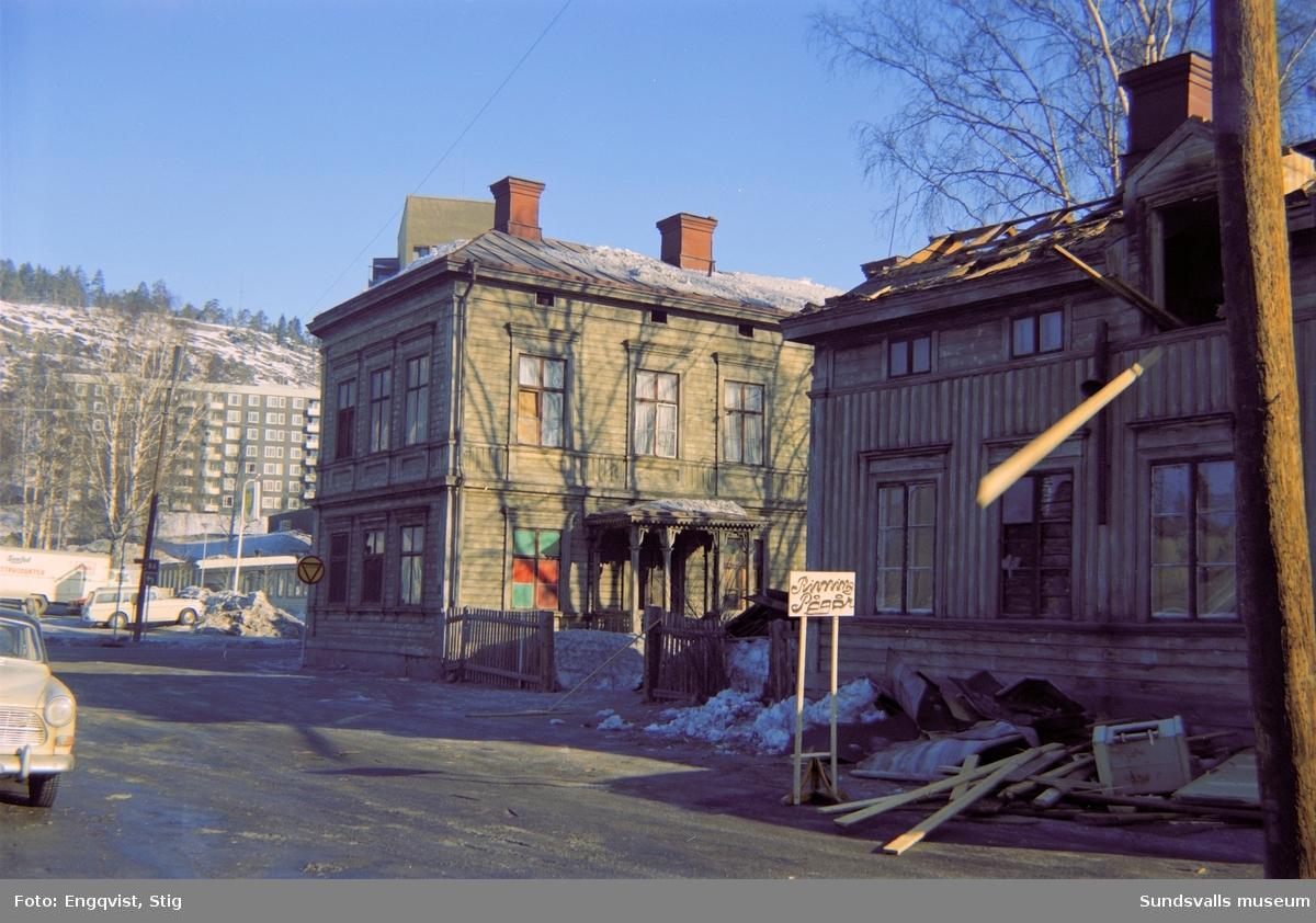 """Hus efter Johannesgatan, under rivningarna av Norrmalm. På skylten står """"Rivning pågår""""."""
