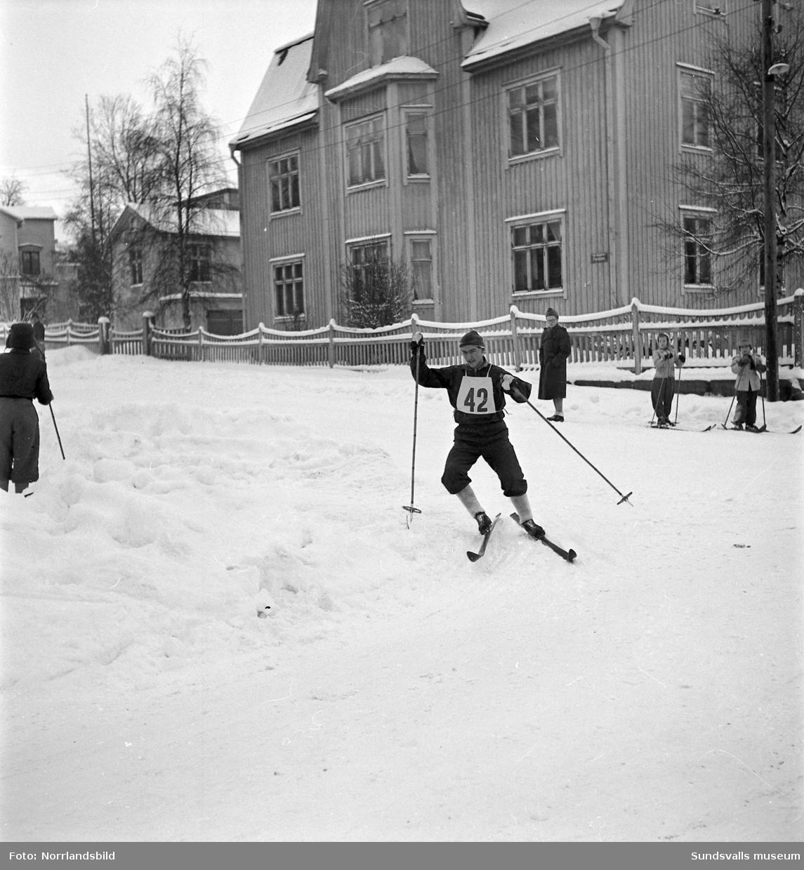 Propagandalopp på skidor i centrala Sundsvall. Målgång på Långgatan mellan GA-skolan och skolparken. Vinnare i loppet blev Esbjörn Wohlin från Hässjö. På den första bilden syns den numera rivna fastigheten på tomten Borgaren 6 invid Skolhusallén där det numera (2015) är parkering.