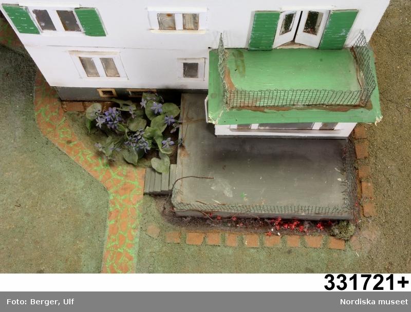 Dockskåp, modell av 1930-talsvilla, hemtillverkat i början av 1970-talet av masonit och pappkartong, med trä- och plastdetaljer. Byggt i fyra våningar med vind, flera sovrum, sällskapsrum, kök, serveringsgång, hall, källare med tvättstuga och garage. Huset står på en platta och har både trädgård, terrass och balkonger. Ytterväggar med fönster av genomskinlig plast finns på alla sidor. Våningsplanen går att lyfta av. Delarna hålls ihop av skorstenen som löper genom hela huset. På vinden finns ett flickrum, pappans arbetsplats, wc och förvaringsutrymmen. På andra våningen finns Stellans pojkrum, föräldrarnas sängkammare, balkong, bibliotek, teverum, wc. Första våningen innehåller hall, kök med frukostrum, serveringsgång, vardagsrum, matsal, badrum och wc . Källaren består av tvättstuga, hobbyrum, matkällare, garage, snickarbod.  Tavlor och en del av inredningen sitter fast på väggarna, medan möbler och husgeråd är lösa (se separata nummer för inventarier). /Karin Dern 2011-10-14