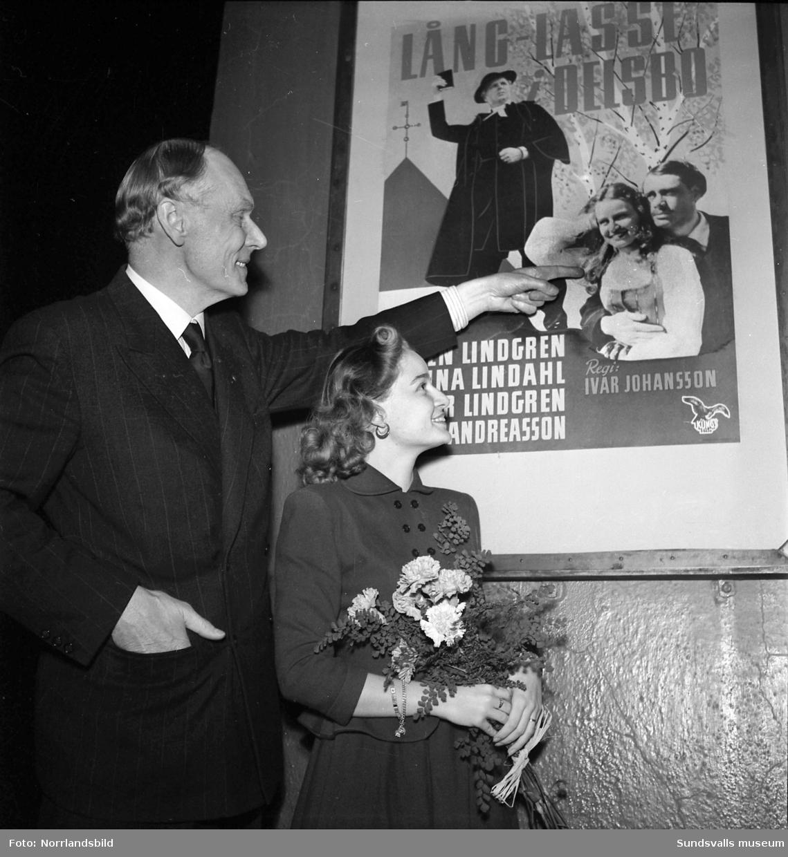 Filmskådespelerskan Ulla Andreasson och direktör Hagelby vid en filmaffisch för filmen Lång-Lasse i Delsbo (premiär 1949).
