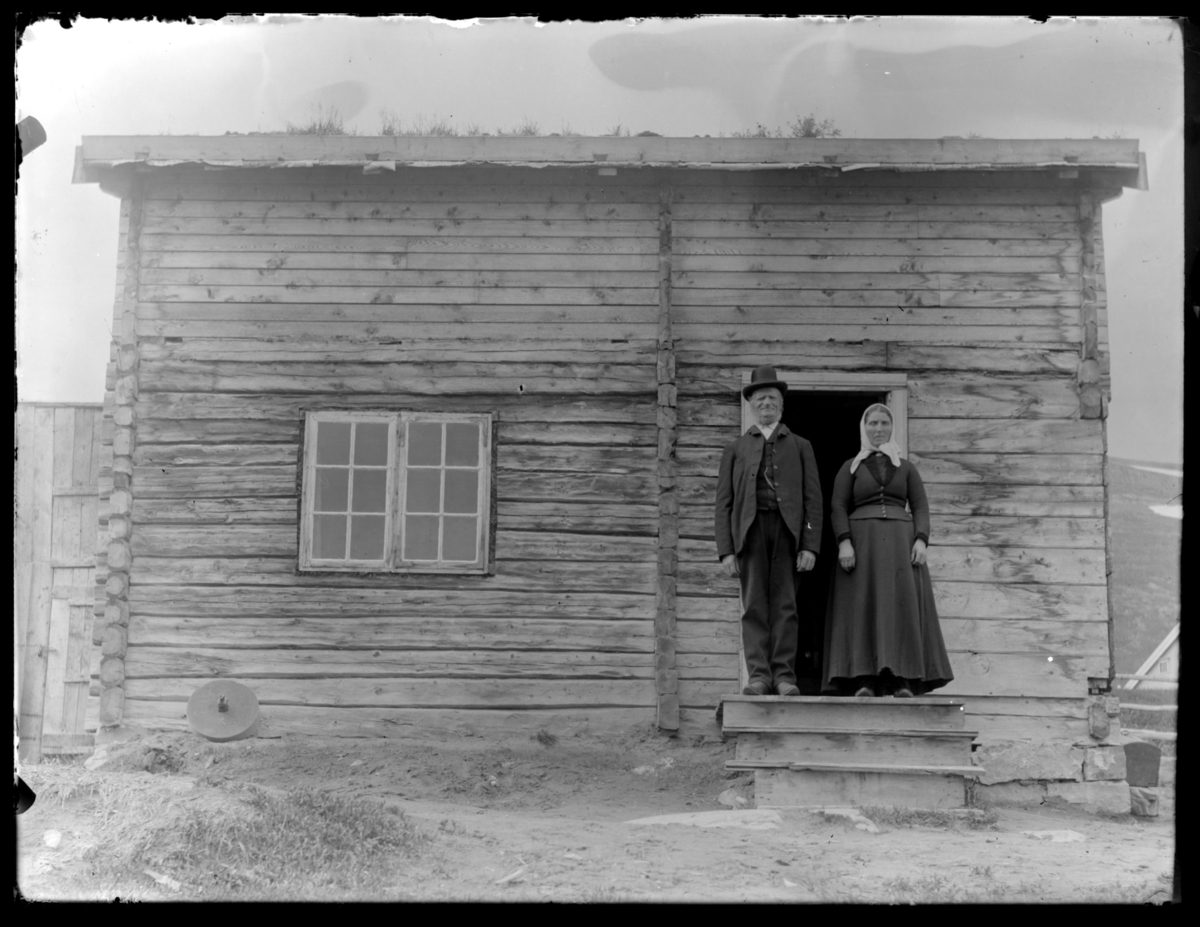 Kirketjener Ole Einarsen og kona Kristina på trappa til et tømmerhus