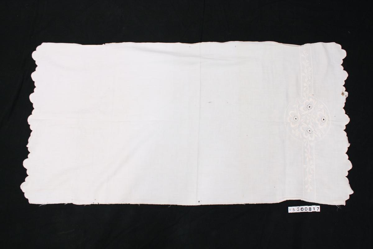 Hvit på hvit brodert bølgekant nederst på kortsidene. På den ene kortsiden er det brodert inn hvit på hvit en dekorkant med sirkel i midten med plantedekor.