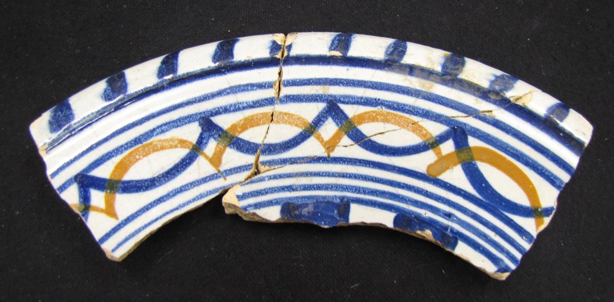 BRÄTTE. LUNDBERG IIa. Fajans, en av 24 mynningsdelar. Dekor med vit botten och blå detaljer.  År 1943 utförde arkeolog Erik B. Lundberg från riksantikvarieämbetet en arkeologisk utgrävning av den forna staden Brätte.