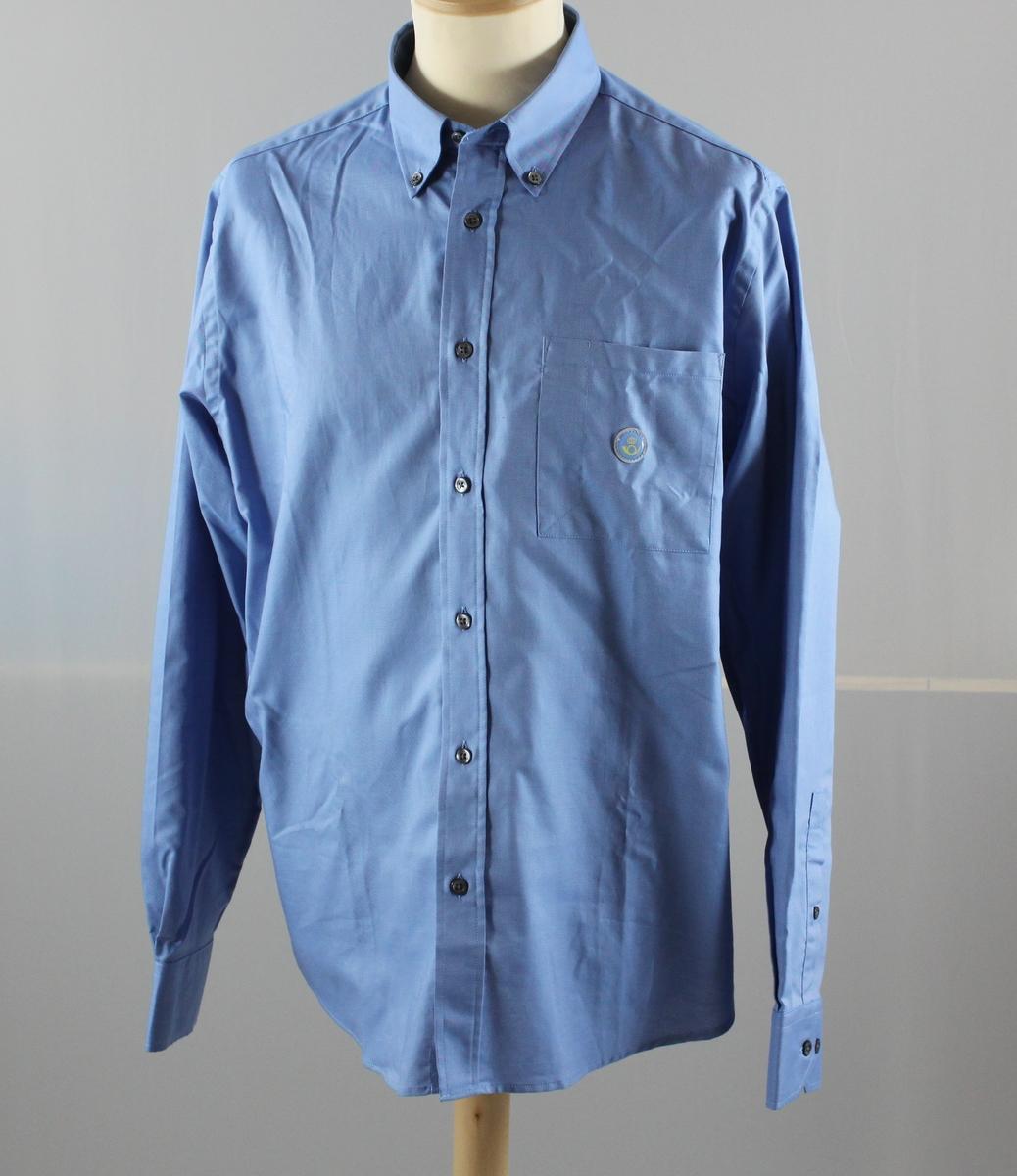 """Skjorta i ljusblått med långa ärmar. En bröstficka till vänster och ett reflexmärke med Postens symbol på den. Märkt """"herr"""" och storlek 40."""
