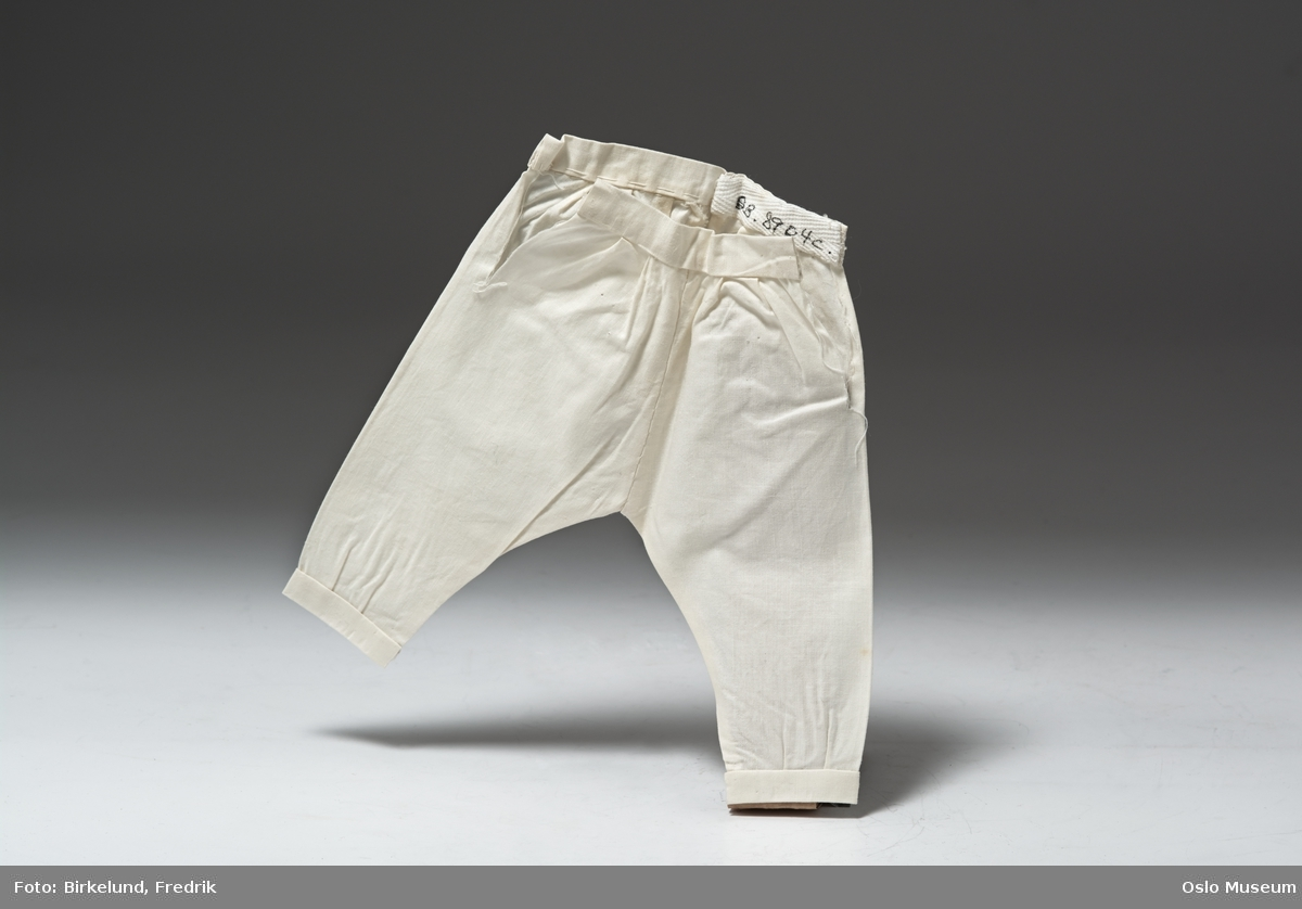 A:Cape. B:Hette C:Underbukse D:Underbukse E-F:Natt/frisérjakke. G:Korsettbeskytter H:Underskjørt J-K:Nattkjole L-M:Nattskjorte