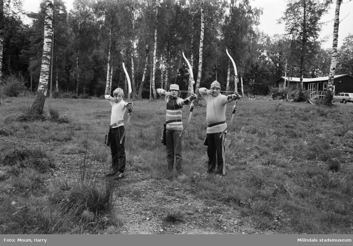 Bågskyttar i Lindome bågskytteklubb, år 1983. Pappa Jan-Erik Lundin (längst t h) koncentrerar sig mot skjutmålet ihop med sönerna Mikael, 12, och (i mitten) Morgan, 14.  För mer information om bilden se under tilläggsinformation.