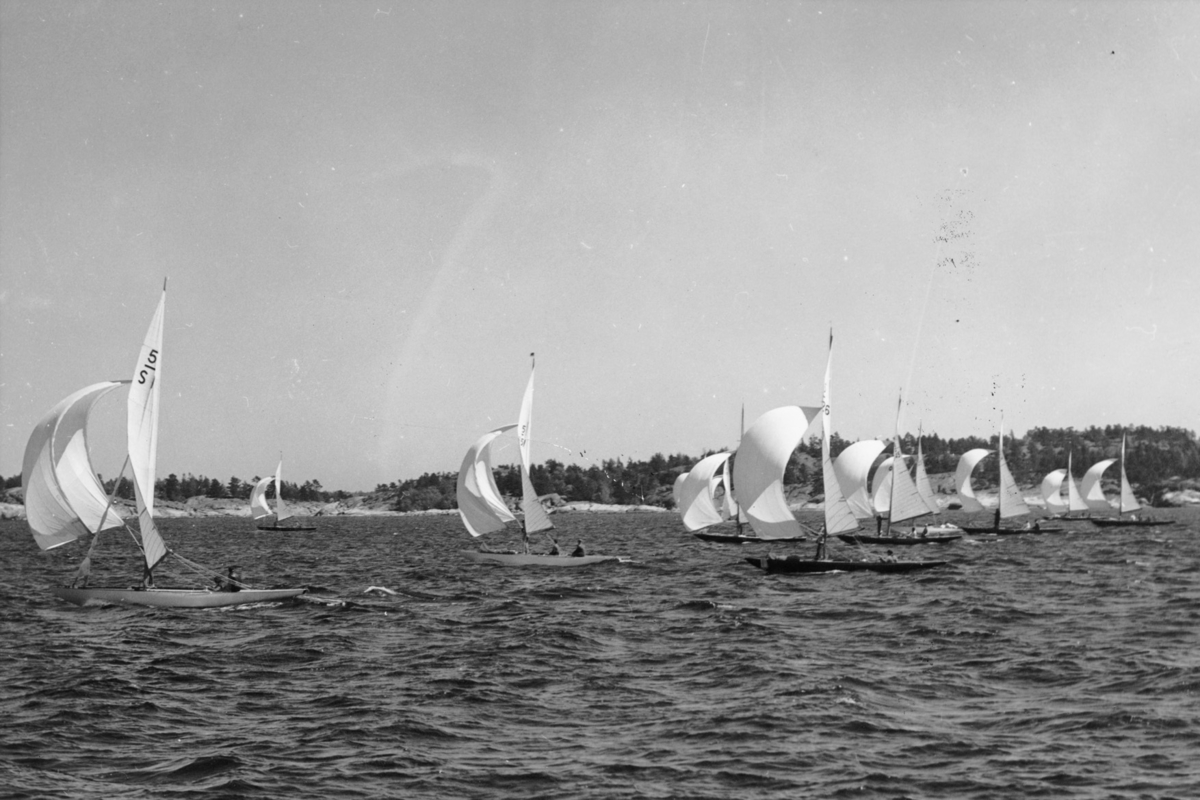 Fartyg: TRIONA                         Bredd över allt 1,90 meter Längd över allt 8,90 meter  Rederi: Salén, Ernst Byggår: 1936 Varv: Stockholms Båtbyggeri Konstruktör: Reimers, Knud H. Övrigt: Från Juniregattans andra dag 15 juni 1941, Kanholmsfjärden. 5-S1 TRIONA längst t v. Båten i mitten med vitt skrov 5-S51 BLÅVINGE, båten med mörkt skrov t h i förgrunden 5-S26 GOING III, båten därbakom 5-S45 DOTTE. Fotografiet återfinns i beskuret skick återgivet i Till Rors årg. 7 (1941) nr 4 s 131.