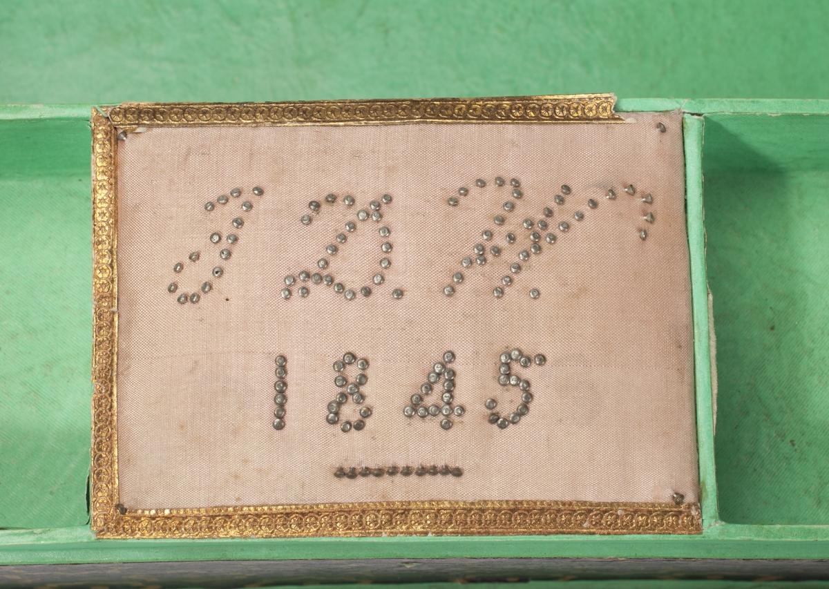 """Smykkeskrin i to etasjer laget av """"sammenpresset papir / papp"""". I nederste er det to små og ett stort rom, samt en skuff med to rom og en liten """"pute"""" med initialene J.D.W. og årstallet 1845."""