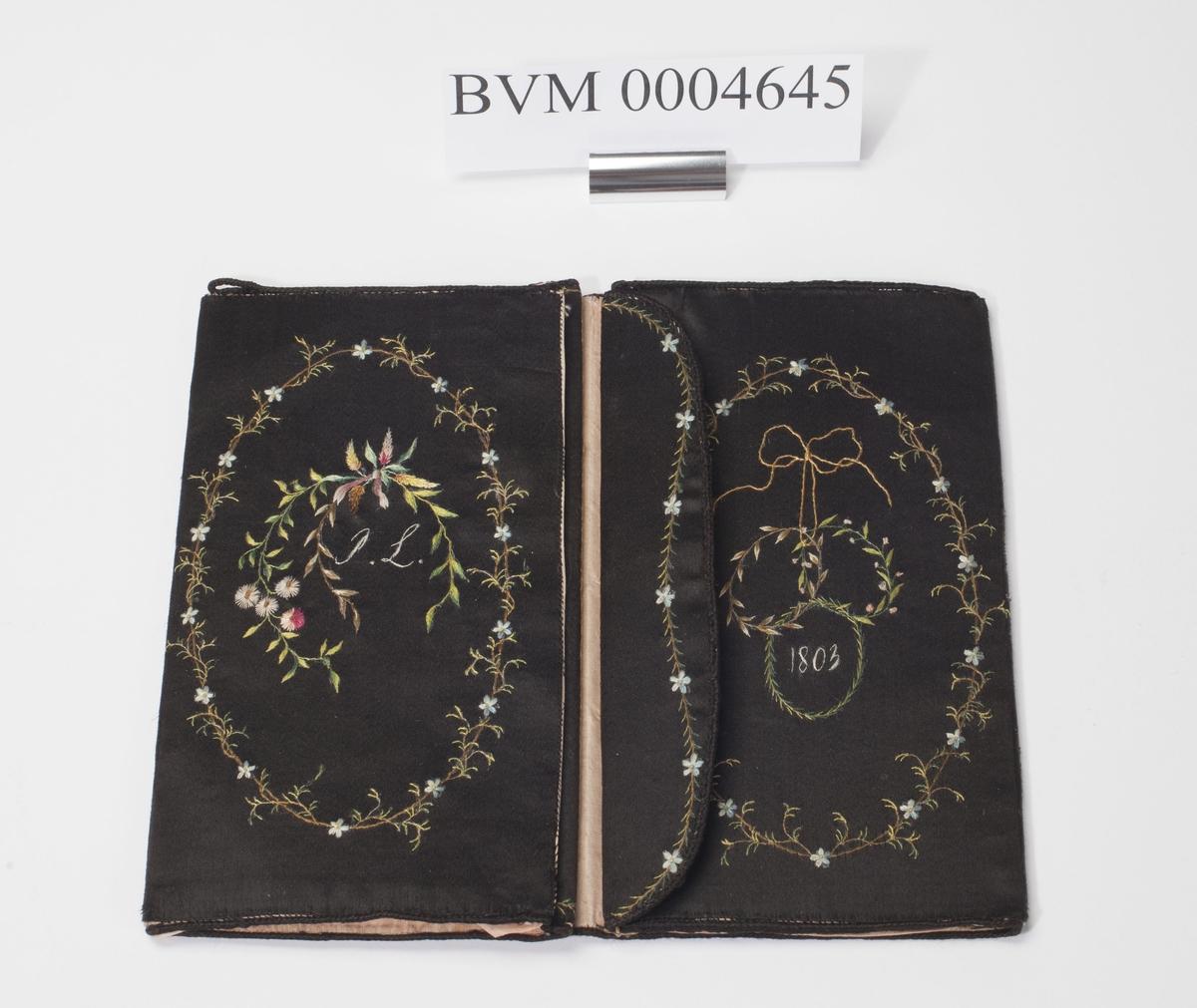 Brodert silketrukket lommebok med fire rom. Utvendig brodert en enkel ring med blomsterdekor. Inne i den ene ringen en bikube og i den andre et brennende alter(?).  Når lommeboken åpnes mer blonmsterdekor og initialene PL og årstallet 1803 brodert inn.