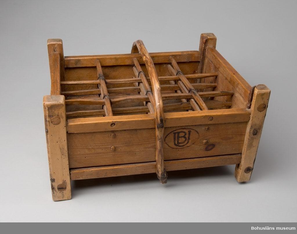 """Rektangulär back för öl eller dricka. Tillverkad helt av trä med hörnståndare av björk, intappade sidor och fack av barrträ av täljda stänger för 12 flaskor sammanhållna av järntråd och med bärhandtag av naturvuxet ämne av ene.  Botten av tre glest satta brädor. Klarlackad. På långsidorna inbränt företagsmärke """"UB""""  - Utsiktens Bryggeri - i en liggande oval ring."""