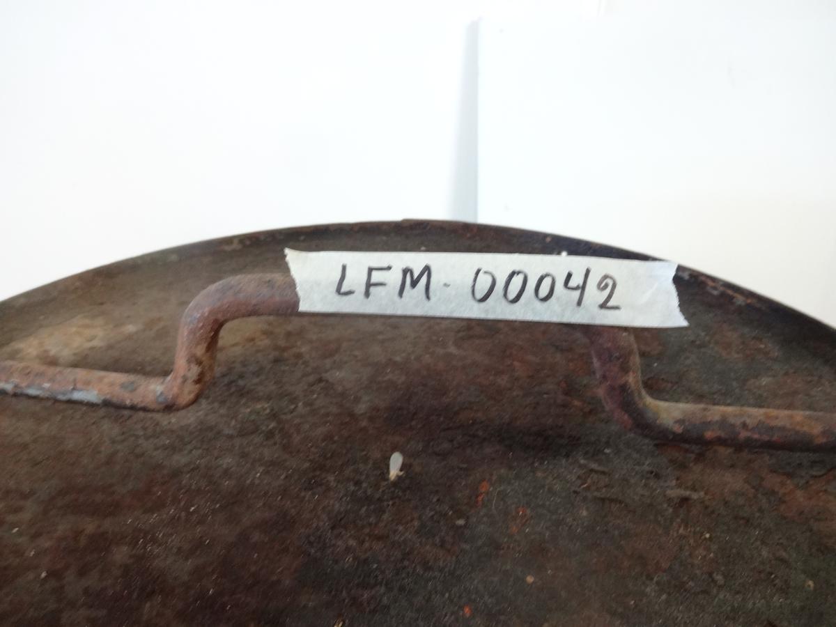 Liten oljetank (50l) med håndtak og åpning på toppen. Brun av rust, men den har vært malt svart.