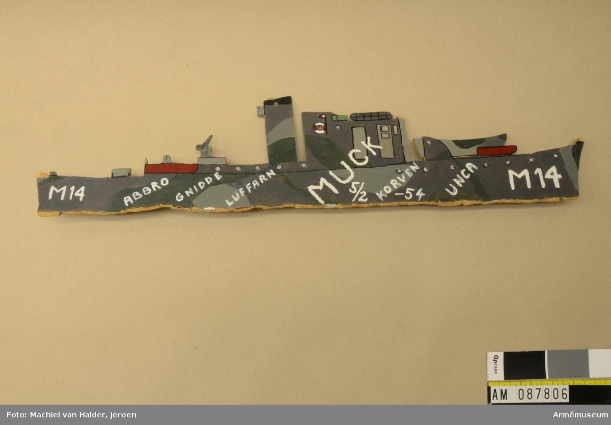 Muckarkam utskuren i plywood i formen av en fartygssiluett.